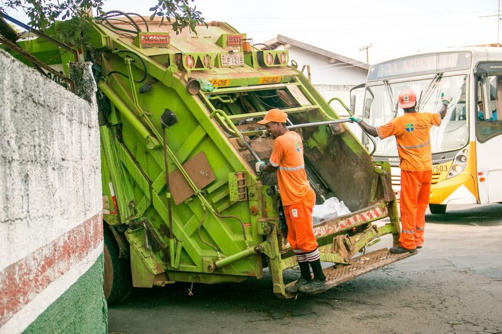 A green garbage collection truck