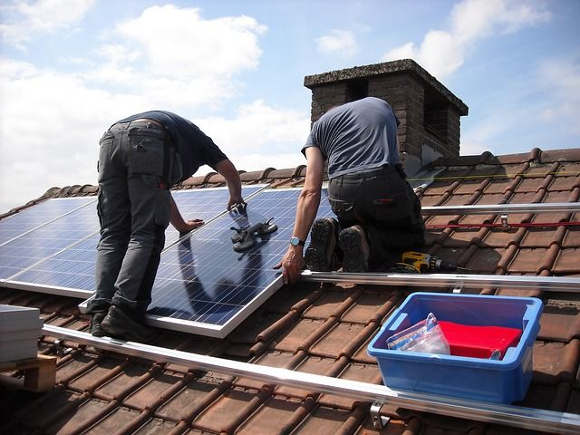 Workers installing solar panels on the roof of a house